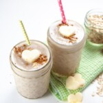 2 glasses of apple pie smoothie with heart apples and cinnamon on top.