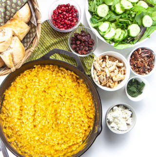 Spread of food on a counter will a big saucepan full of pumpkin risotto.