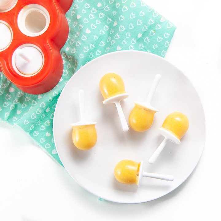 Plate filled with orange vitamin c popsicles.