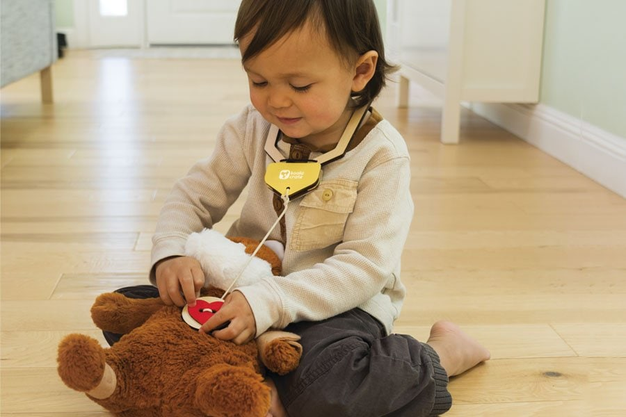 Kid being a vet on a stuffed animal