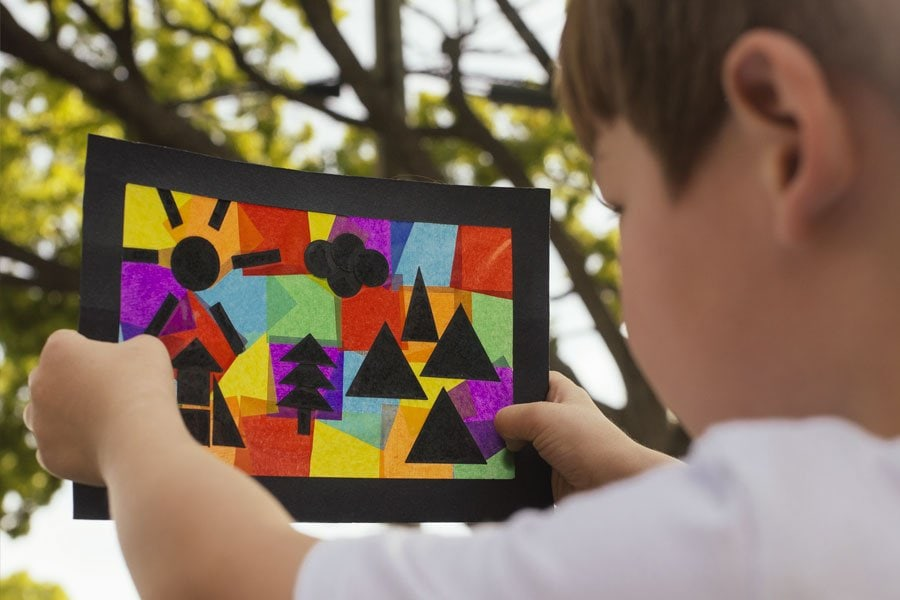 Kid holding up a colorful collage.