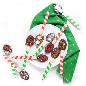 Spoons dipped in chocolate and with toppings spread over a plate and green napkin.