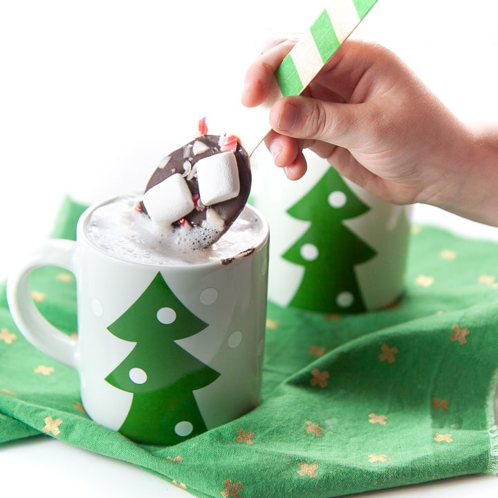 small hand holding a chocolate stirring spoon dunking it in warm milk.