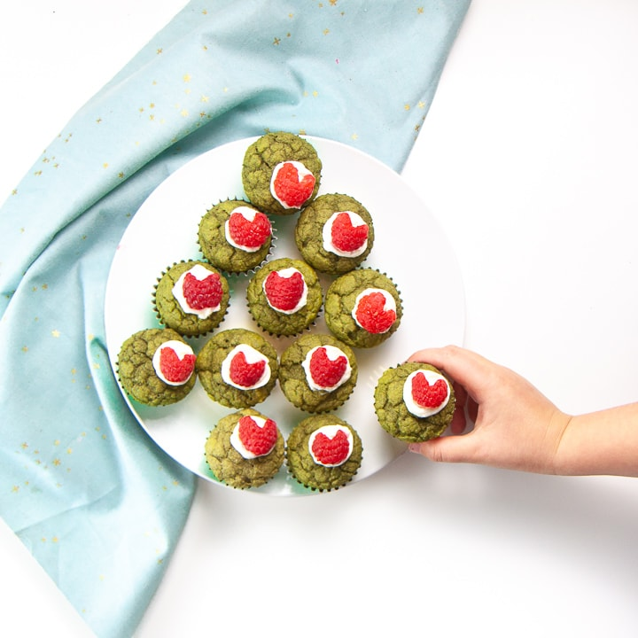 Green Grinch Muffins on a white plate with a small toddler hand reaching out to grab one.