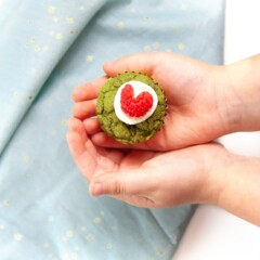 Two small toddler hands holding a mini green grinch muffin.