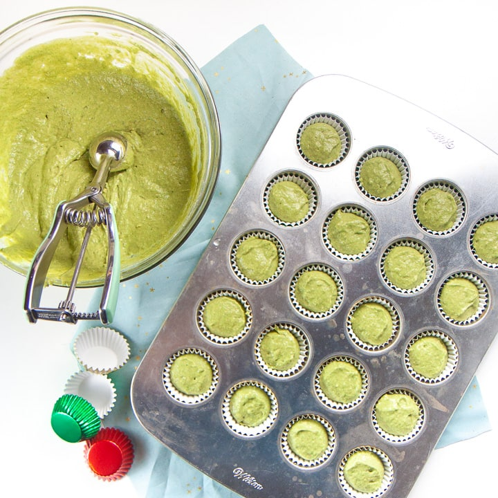 Green muffin batter in a clear bowl with a mini muffin pan full of muffin batter.
