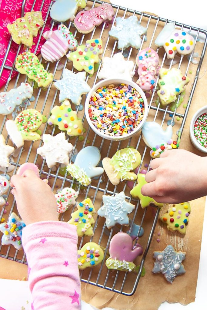 Kids hands decorating gluten free sugar cookies with dye-free sprinkles.
