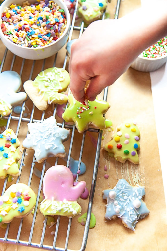 Small hand decorating gluten free sugar cookies with sprinkles.