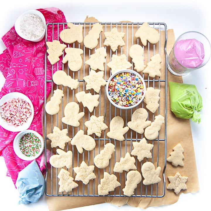 Cooling rack with gluten free and egg free sugar cookies on it with dye free sprinkles and icing around them.