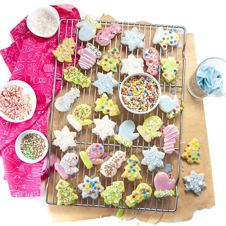 Cooling rack with decorated sugar cookies on it with dye free sprinkles and icing.