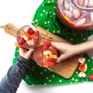 2 kids with glasses of Christmas punch.
