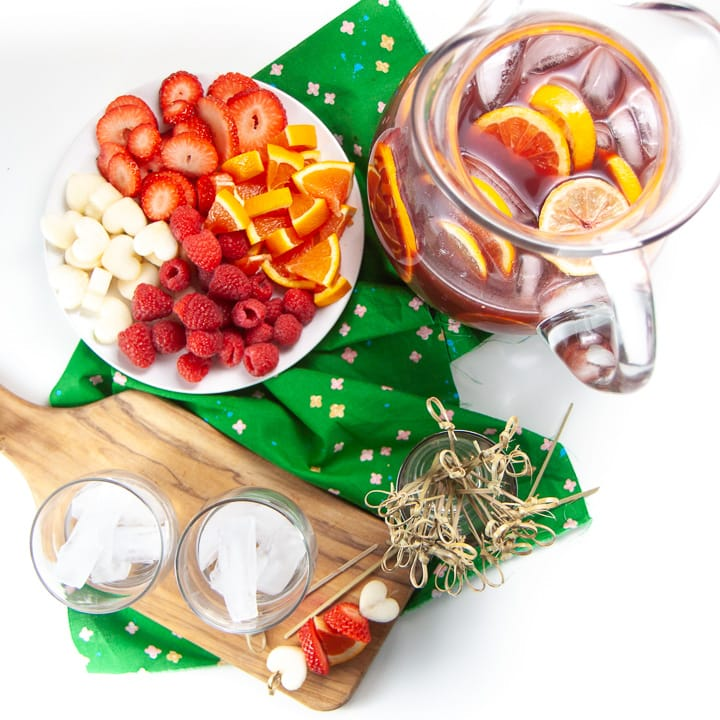 Spread of pitcher with Christmas punch and a plate with fruit and sticks for kids to make them.