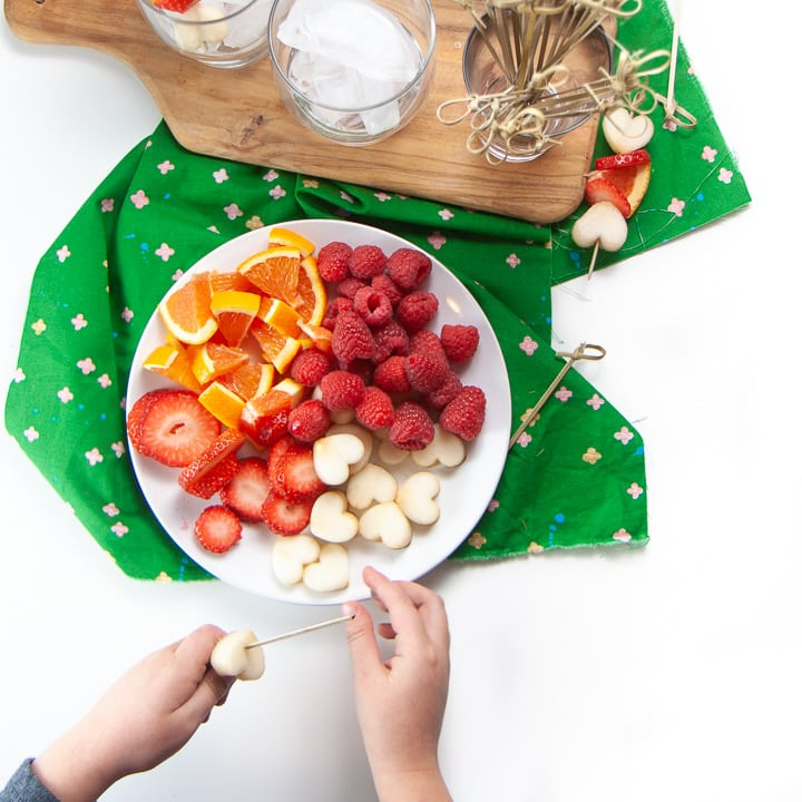 Round white plate with assortment of fruit on it with small kids hands making their own fruit sticks.