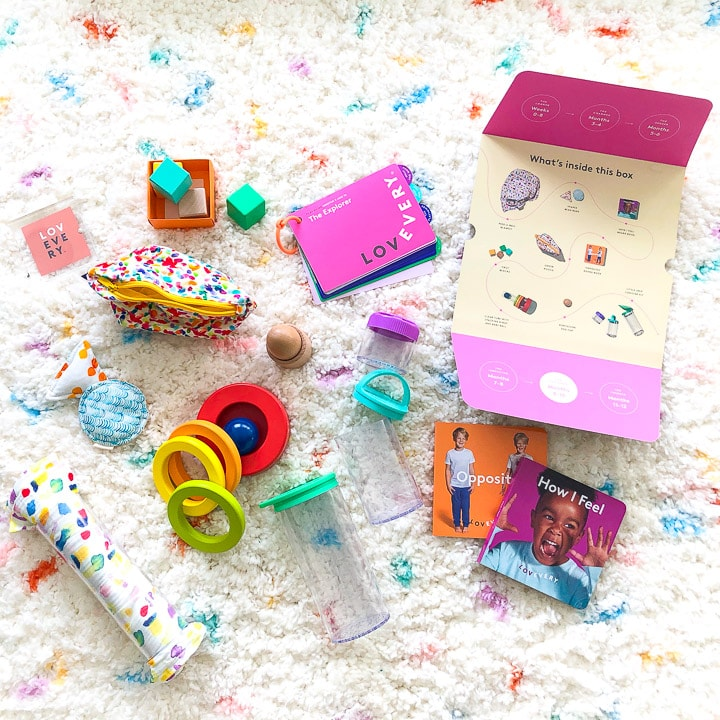colorful baby toys scattered on a white and dotted carpet.