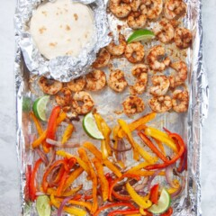 Sheet pan with cooked shrimp tacos and tortillas on top.