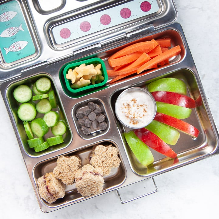 school lunch box filled with apples and spiced dip.