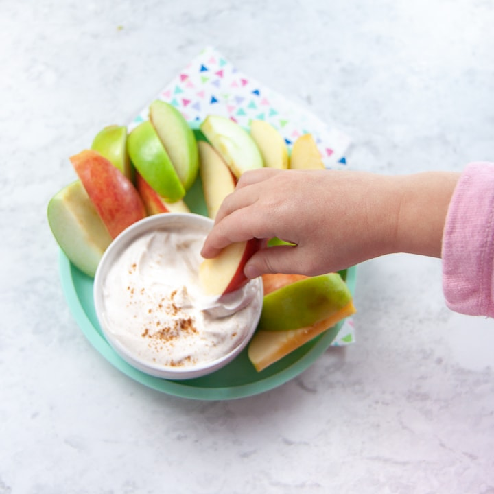 Toddler hands dipping an apple into healthy spiced dip.