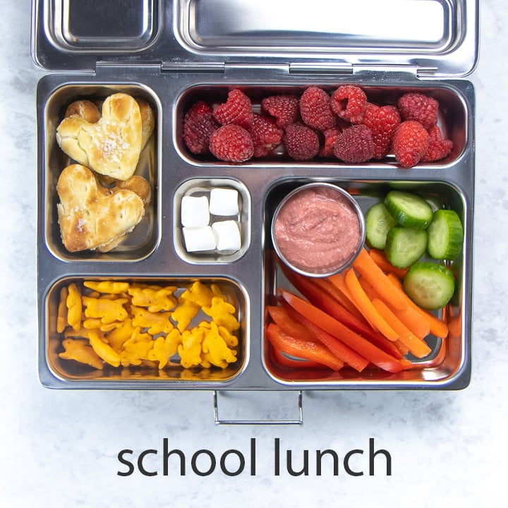 metal school lunch box full of beet hummus, dippers and other snacks.
