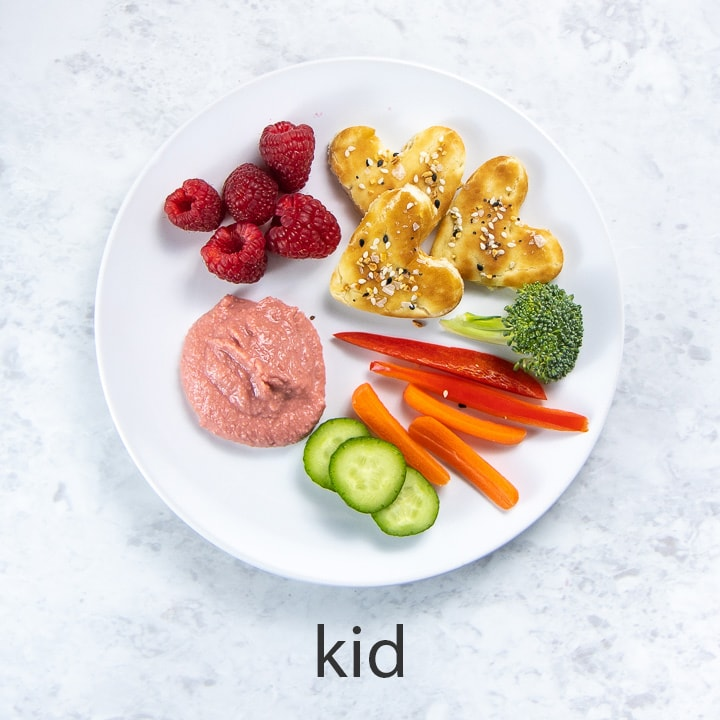white round kid plate full of beet hummus and dippers.