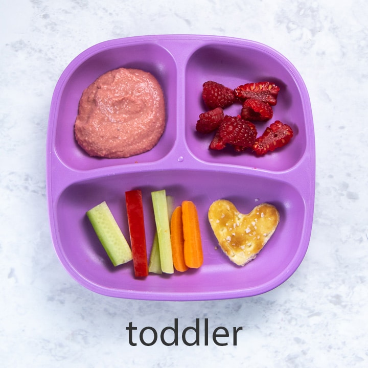 purple toddler plate filled with beet hummus, veggies and snacks.