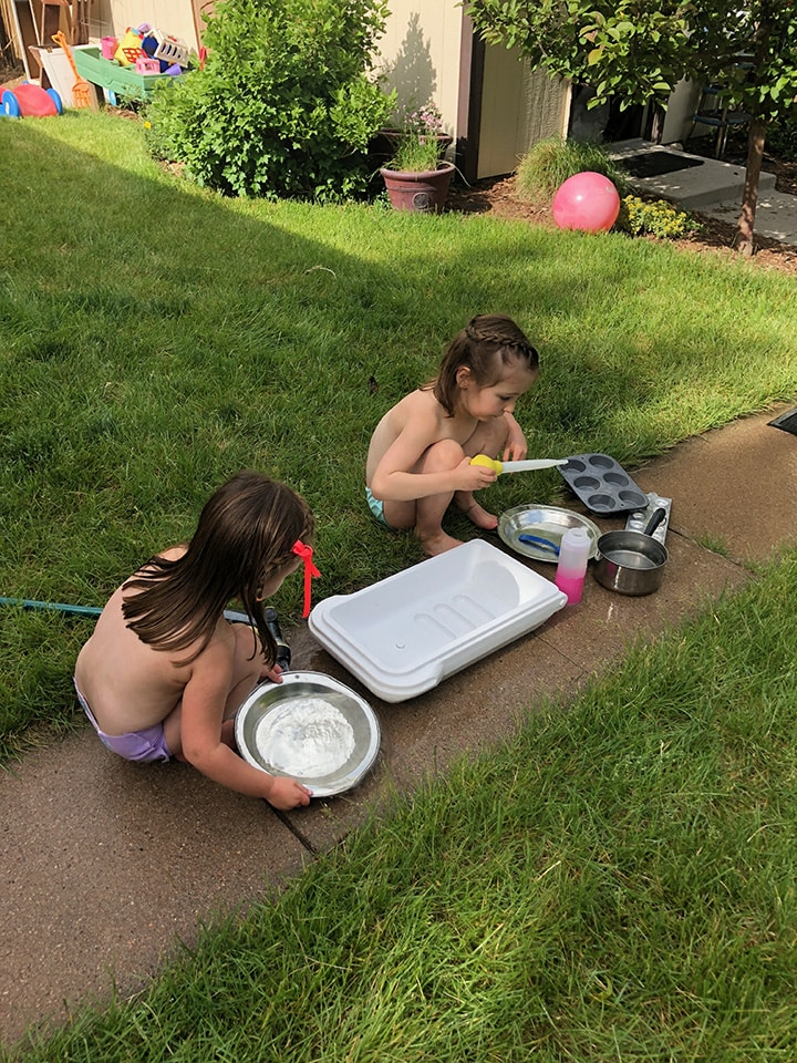 2 girls cleaning up their mud kitchen outside.