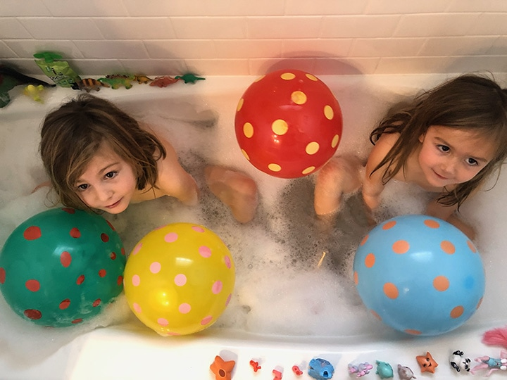 2 girls in a bath tub with balloons.