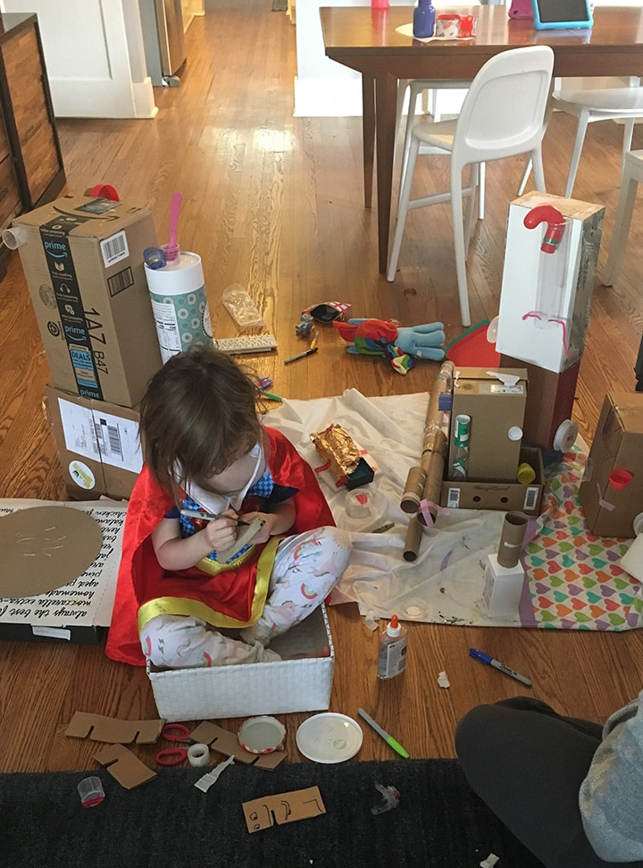 girl upcycling boxes into a robot as a fun at home activity.