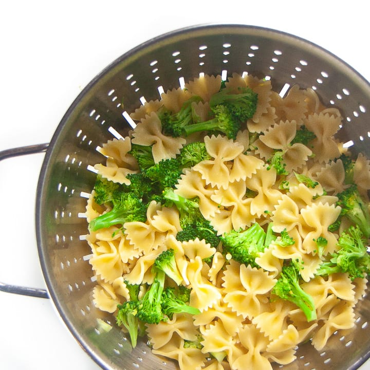 Colander with strained pasta and broccoli