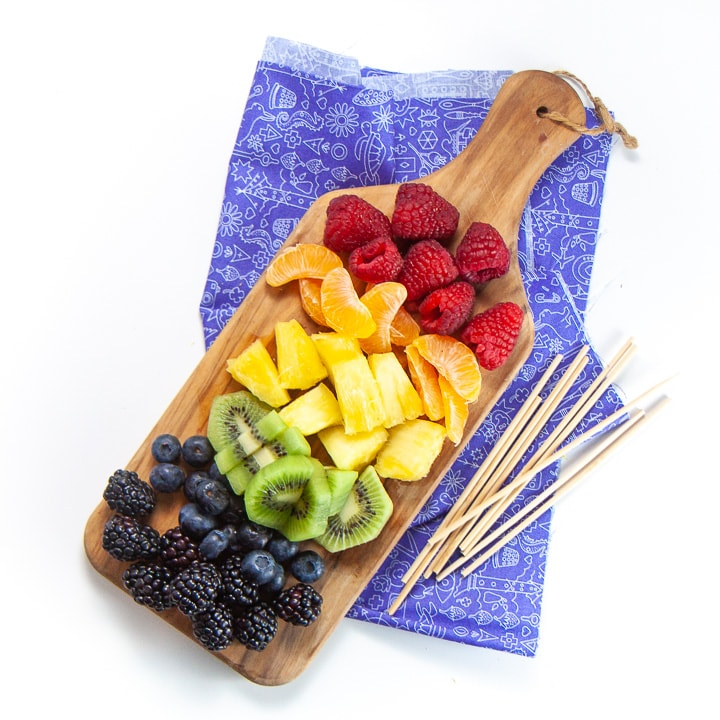 cutting board with rainbow fruit and skewers