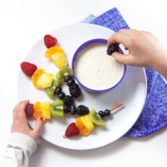 rainbow skewers on a plate with a bowl of yogurt dip.