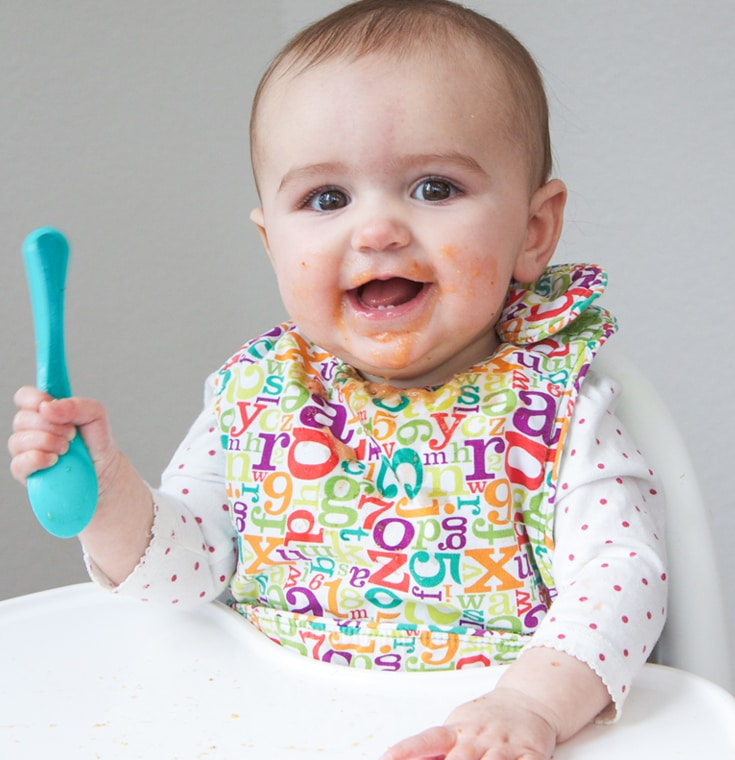 Baby in highchair with baby puree all over her face.