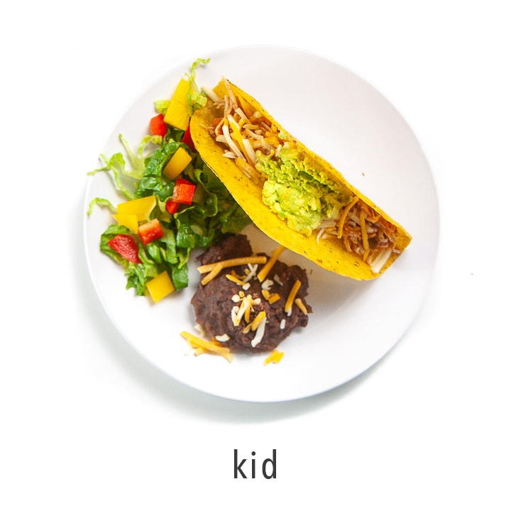 A kids plate full of tacos and sides.
