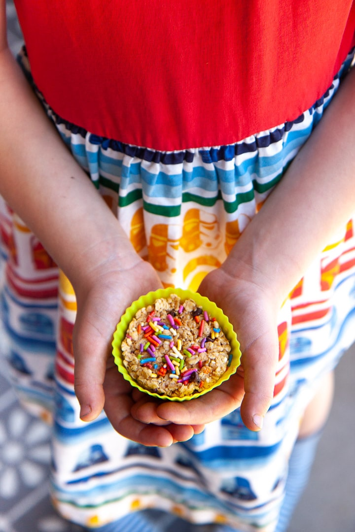 Girl holding a funfetti granola cup in a colorful dress
