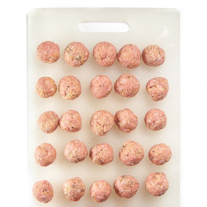 chicken meatballs on a cutting board rolled into balls