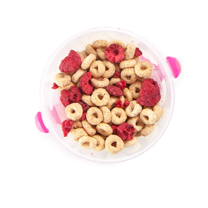 A toddler snack cup filled with cereal and freeze dried berries.