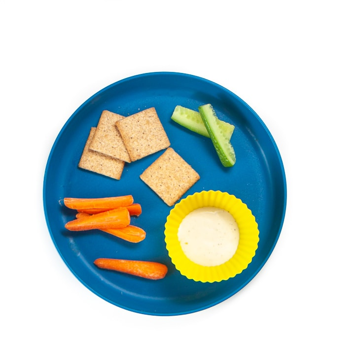 Toddler plate filled with cut veggies, crackers and dips.