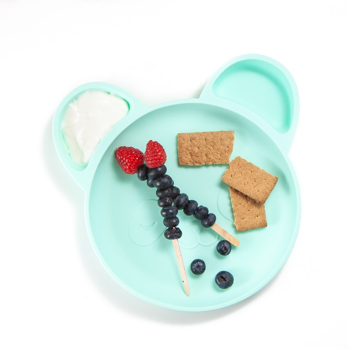 Toddler plate with berries, crackers and dip.