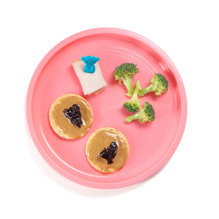 Toddler or kid snack of pb&j crackers, cut broccoli and rolled up turkey.