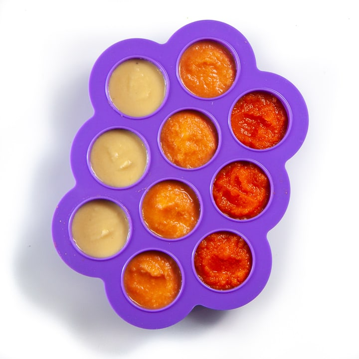 Purple baby food storage container with three different baby purees inside.