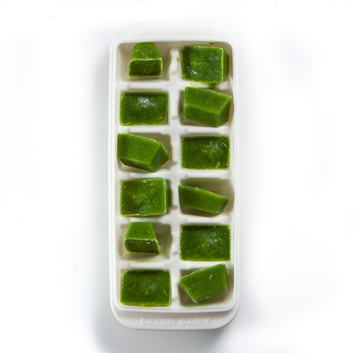 white baby food storage container with green baby food frozen cubes.