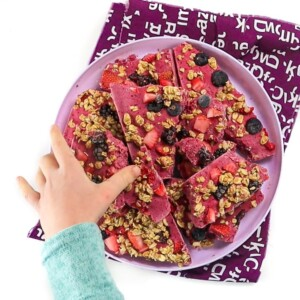 Girl reaching for a piece of berry granola bark.