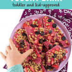 Graphic for Post - berry granola yogurt bark - toddler and kid approved with small kids hand reaching into a plate full of yogurt bark to pick one up.