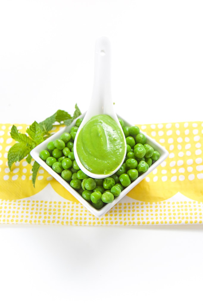 Pea puree sitting on a tray of fresh peas with mint tucked behind it.
