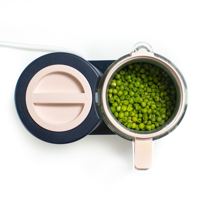 Black and pink beaba babycook with steamed peas inside the glass container.
