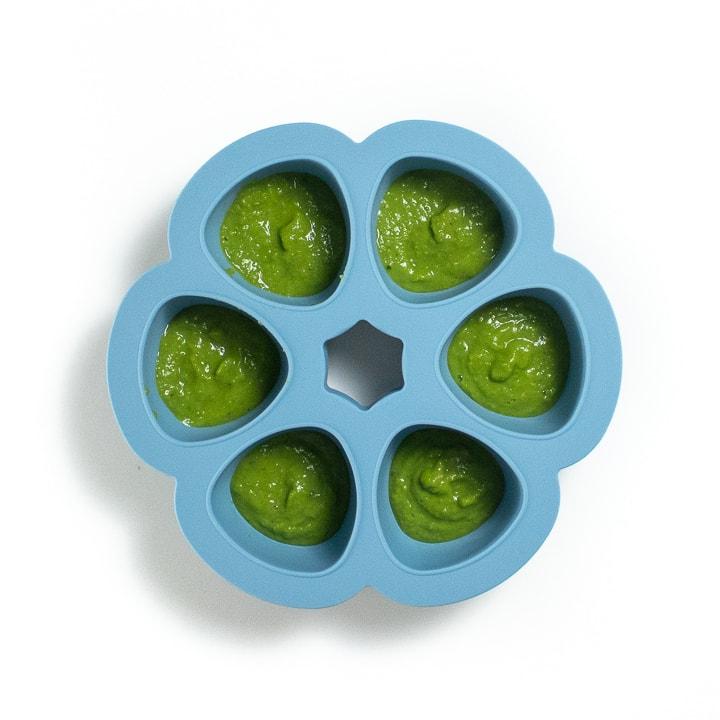 A blue freezer tray with pea puree inside.