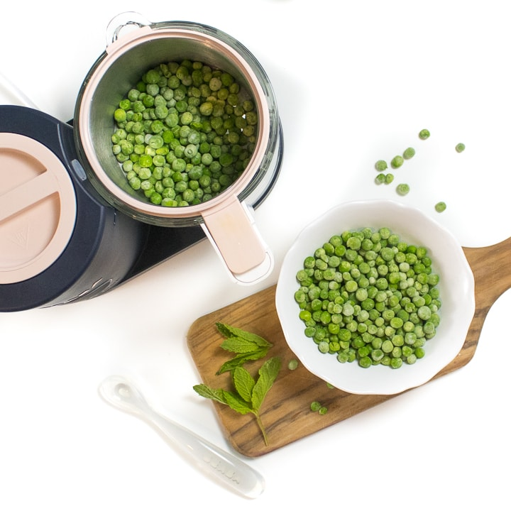 Spread of a black and pink BEABA babycook with a cutting board with peas and mint on it.