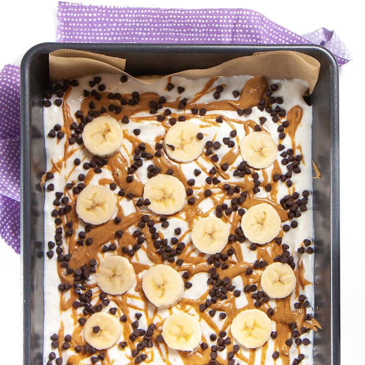 A baking dish of banana, peanut butter and chocolate frozen yogurt bark for toddlers and kids.