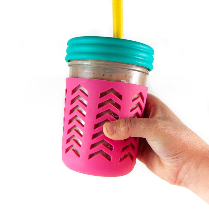 kids hand holding a colorful smoothie cup filled with hidden-veggie smoothie