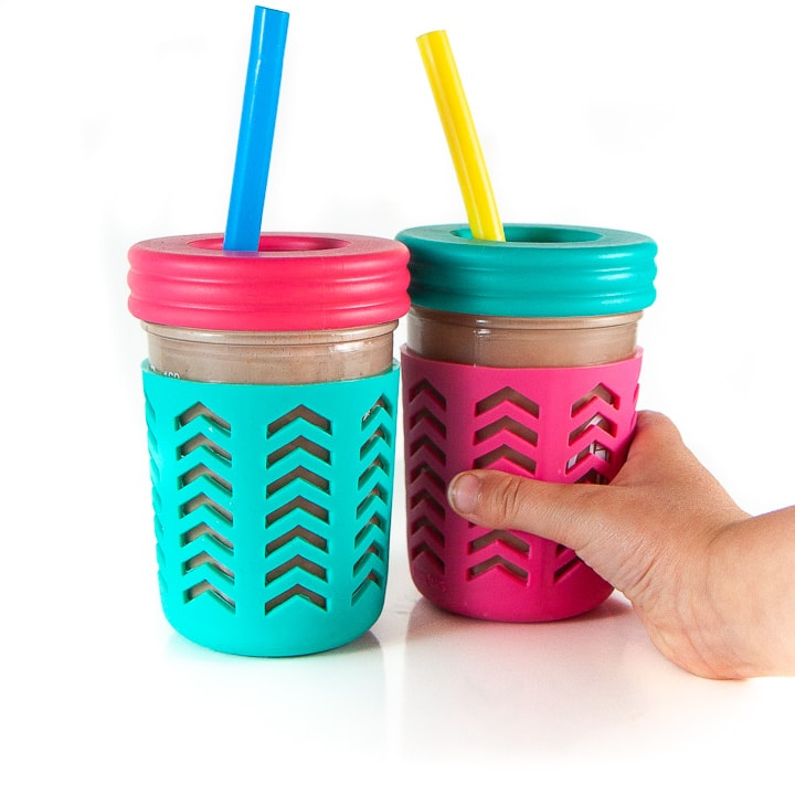2 smoothie cups with a small kids reaching towards one of the cups.