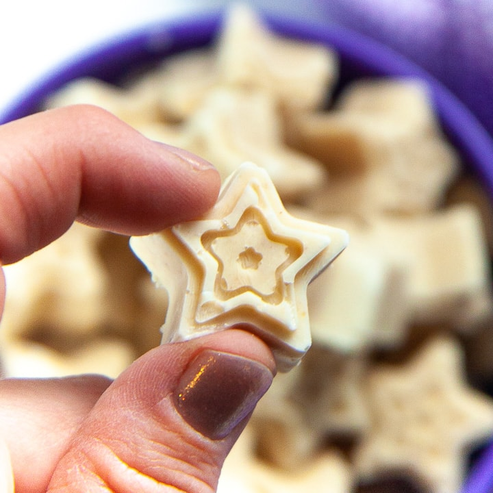 Fingers holding up a star shaped melts for baby.